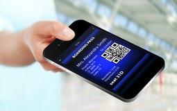 Remettez tenir le téléphone portable avec la carte d'embarquement mobile sur l'aéroport Photo libre de droits