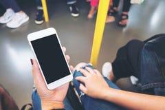 Remettez tenir le téléphone portable blanc avec l'écran noir vide dans le souterrain avec beaucoup de personnes à l'arrière-plan Photos libres de droits