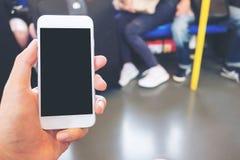 Remettez tenir le téléphone portable blanc avec l'écran noir vide dans le souterrain avec beaucoup de personnes à l'arrière-plan Images libres de droits