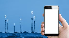 Remettez tenir le téléphone portable l'écran, les tours de télécommunication et le fond blancs de signe d'icônes d'emplacement photos libres de droits