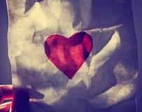 Remettez tenir un coeur de papier peint jusqu'au soleil pendant le sunse Image stock