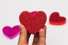 Remettez tenir un coeur rouge de scintillement contre les coeurs brouillés sur le fond blanc Photo stock
