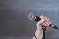 Remettez tenir un microphone dans une image conceptuelle Image libre de droits