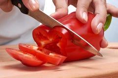 Remettez tenir un poivron doux rouge coupé en tranches par couteau Photographie stock