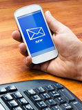Remettez tenir un smartphone avec un nouveau message Image stock