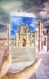 Remettez tenir un smartphone avec une photo de cathédrale de Batalha dedans Photo libre de droits