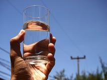 Remettez tenir un verre de l'eau contre un ciel bleu Image stock