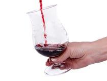 Remettez tenir un verre en lequel du vin est versé Image libre de droits