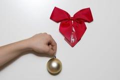 Remettez tenir une boule d'or décorative sous un ruban rouge Image stock