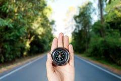 Remettez tenir une boussole magnétique au-dessus d'une vue de paysage Images stock