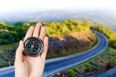Remettez tenir une boussole magnétique au-dessus d'une vue de paysage Image stock