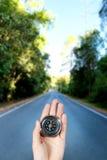 Remettez tenir une boussole magnétique au-dessus d'une vue de paysage Image libre de droits