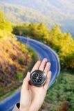 Remettez tenir une boussole magnétique au-dessus d'une vue de paysage Photographie stock
