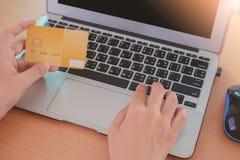 Remettez tenir une carte de crédit et saisir des données dans un ordinateur portable d'ordinateur photos libres de droits