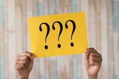 Remettez tenir une note de papier avec le point d'interrogation image libre de droits