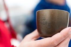 Remettez tenir une tasse avec des symboles chinois là-dessus Photo libre de droits