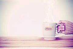remettez tenir une tasse de tasse de café avec l'étiquette heureuse de mot sur le tabl en bois Image stock