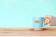 remettez tenir une tasse de tasse de café avec l'étiquette heureuse de mot sur le tabl en bois Images libres de droits