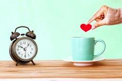 remettez tenir une tasse de tasse de café sur la table en bois, Romance et l'amour Photo libre de droits