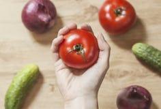 Remettez tenir une tomate rouge avec des légumes à l'arrière-plan Photo stock