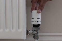Remettez tourner le bouton de radiateur pour abaisser la chaleur et les économies sur la consommation Photo stock