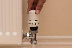 Remettez tourner le bouton de radiateur pour abaisser la chaleur et les économies sur la consommation Photo libre de droits