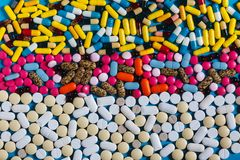Remi le pillole bianche e colorate su fondo blu, vista superiore Concetto della medicina di creatività Immagini Stock Libere da Diritti