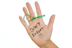 Reminder. A string tied around a finger along with a note written on the palm of a hand that says don't forget Stock Photo