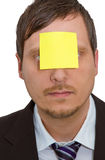 Reminder. Photo of a man's face with a blank yellow sticky note stuck to his forehead Royalty Free Stock Image