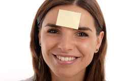 Reminder. Photo of a pretty smiling woman's face with a blank yellow sticky note stuck to her forehead Royalty Free Stock Photos