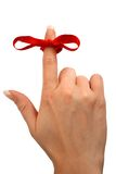 Reminder Bow. Red bow tied on a finger as a reminder royalty free stock photo