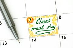 Reminder Cheat Meal Day in calendar with green pen. Close-up stock photo