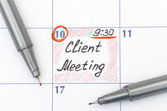Reminder Client Meeting in calendar with pens Stock Image