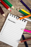 Reminder with copyspace and colorful pencils on wooden table Royalty Free Stock Photography