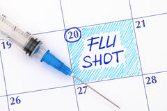 Reminder Flu Shot in calendar with syringe. Close-up Stock Photography