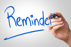 Reminder hand writing with a blue mark on a transparent board Stock Images