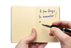 Reminder note. Writing a reminder note in the notebook Stock Photography