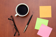 Reminder notes, pen and glasses with cup of coffee Stock Images