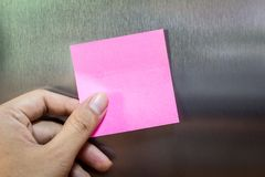 Reminder sticky note on refrigerator. Door Stock Photography