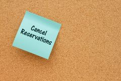 Reminder to cancel your reservations. A reminder to cancel reservations, Bulletin board with a teal sticky note with text Cancel Reservations stock photography
