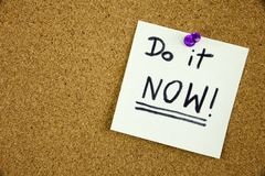 A reminder to do it now message, Bulletin board with a blue sticky note with text Do it Now Stock Photo