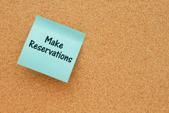 Reminder to make reservations. A reminder to make reservations, Bulletin board with a teal sticky note with text Make Reservations Royalty Free Stock Image
