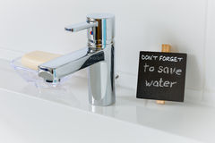 Reminder to save water in the bathroom Stock Image