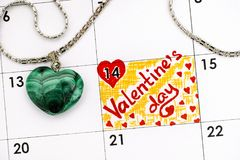 Reminder Valentines Day in calendar with green malachite heart o. Reminder Valentine`s Day in calendar with green malachite heart on white golden chain. Close-up royalty free stock photos