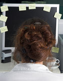 Reminders. Young woman at computer screen, filled with messages and reminders Royalty Free Stock Images