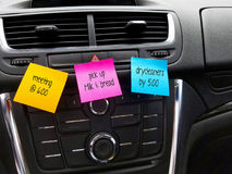 Reminders on colorful sticky notes in car. Colorful sticky notes with text reminders stuck on car dashboard Stock Image