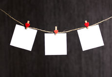 Reminders note hanging on clothespin on clothesline. Three reminders note hanging on clothespin on clothesline - isolated on grey dark background Royalty Free Stock Images