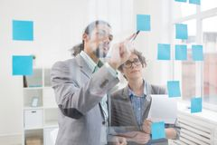Reminding notes. One of colleagues pointing at reminder on blue notepaper on transparent board Royalty Free Stock Photo
