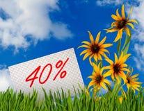 Remise à vendre, remise de 40 pour cent, belles fleurs dans le plan rapproché d'herbe Images stock