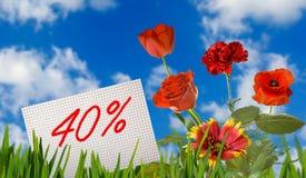 Remise à vendre, remise de 40 pour cent, belles fleurs dans le plan rapproché d'herbe Photos libres de droits